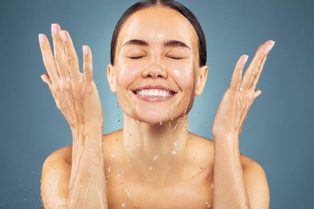 woman splashing water on face smiling